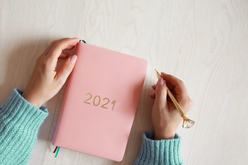 Kobieta trzymająca długopis nad kalendarzem. Jak się nie zniechęcać realizując noworoczne postanowienia.