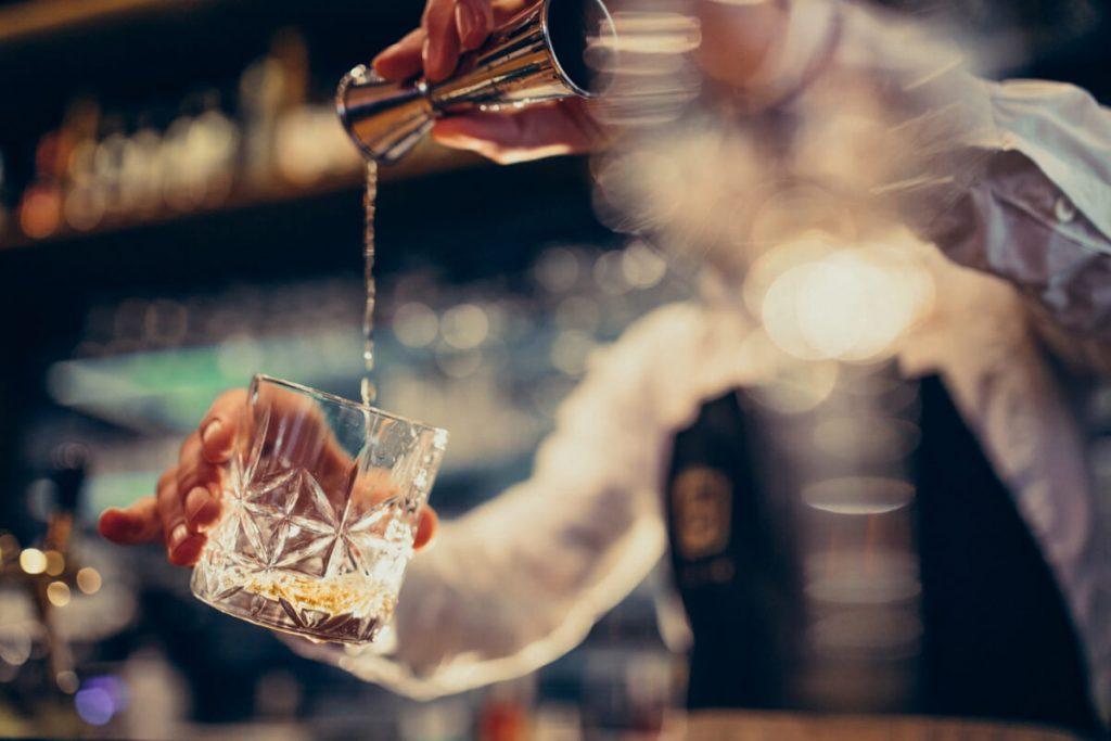Barman przygotowuje drink. Objawy alkoholizmu - sprawdź, zanim wszystko stracisz