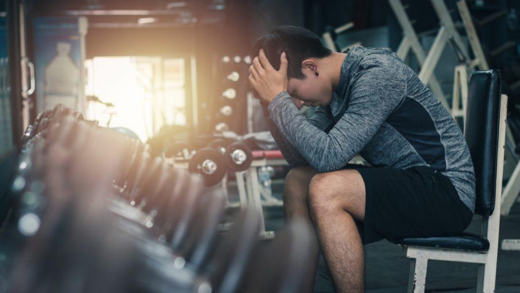 Młody chłopak z głową w dłoniach. Uzależnienie od ćwiczeń - czym się objawia?