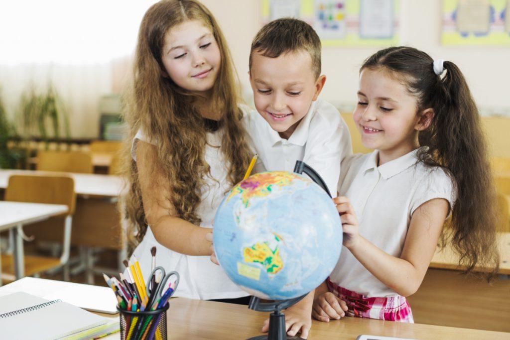 Dzieci przy globusie. Motywowanie dziecka - jak robić to dobrze i skutecznie