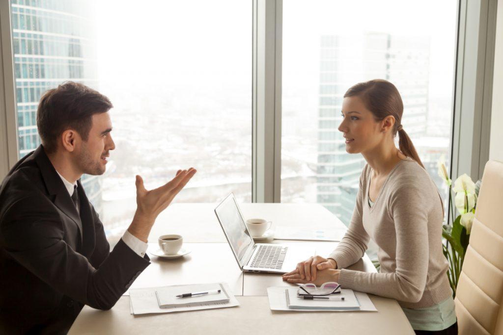 Kobieta i mężczyzna dyskutują w pracy. Uwaga. Karierowicz! - jak sobie z nim poradzić?